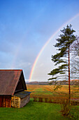 Rural scene, a rainbow in the sky, after rain., Rainbow over a shed or barn