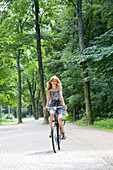 Pretty blonde woman riding a bicycle in park
