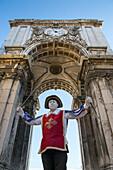 Street performer underneath Arco da Victoria victory arch at Praca do Comercio square in Baixa district, Lisbon, Lisboa, Portugal