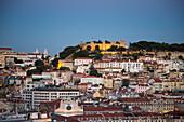 View from Miradouro Sao Pedro de Alcantara in Chiado district across Baixa district and Castelo de San Jorge, St. George's Castle, at dusk, Lisbon, Lisboa, Portugal