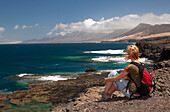 Woman sitting on rocks, looking out to sea, Nature Reserve, Jandia, Fuerteventura, Canary Islands, Spain, Europe