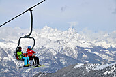 Two people in a ski lift, Pila ski resort, Aosta with Matterhorn, Aosta Valley, Italy