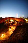 Gäste grillen auf der Holzterrasse am Abend mit Öllampen, Hotel Areias do Seixo, Povoa de Penafirme, A-dos-Cunhados, Costa de Prata, Portugal