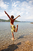 Boy in crane pose in shallow waters, bay near Hotel Sipan, Sipanska Luka, Sipan island, Elaphiti Islands, northwest of Dubrovnik, Croatia