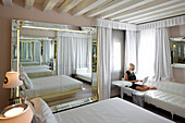 Woman using a laptop in hotel suite, Venice, Veneto, Italy