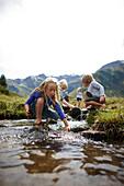 Children playing in a stream along the Nassfeld National Park trail, Nassfeld alp, Gastein valley, Bad Gastein, St. Johann im Pongau, Salzburg, Austria