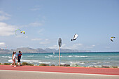Tourists walking along a bike lane next to the coastal road, kite surfer near Club Pollentia, Badia de Pollenca near Alcudia, Mallorca, Balearic Islands, Spain