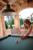 Girl playing billiards at a roofed terrace, Finca Raims, Algaida, Mallorca, Balearic Islands, Spain