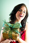 A tight portrait of a smiling 19 year old brunette woman holding a boxed wrapped as a christmas present.