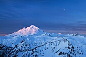 The moon hangs over Mount Baker, 10,781 ft 3,286 m while the snows and glaciers glow in the light of a winter dawn  North Cascades Washington