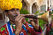 Male actor in turban playing horn Amber Fort near Jaipur Rajasthan India