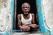 A Cuban man, the Palo Monte priest, wearing a typical red and white bracelet, looks out of the window in Havana, Cuba, August 19, 2009  The Palo religion Las Reglas de Congo belongs to the group of syncretic religions which developed in Cuba amongst the b