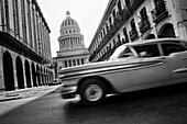 An American classsic car from the 1950s passing along the street in front of The Capitol El Capitolio, Havana, Cuba, 15 August 2008  El Capitolio is a neoclassical building modeled after the U S  Capitol building in Washington and the Pantheon in Paris  C