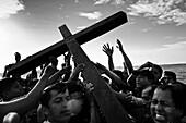 Catholic followers carry the wooden cross in the sea during the annual Holy Week ritual Lavado de la cruz in Santa Elena, Ecuador, 3 April 2012
