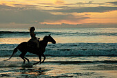 A female rider is silhouetted against the ocean as the sun sets
