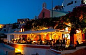 Night exposure after sunset of warm restaurant with tourists on cliff of beautiful Oia in Santorini Greece in Greek Islands