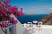 Postcard scene of two lonely chairs and pink flowers on terrace with table ready for tourists in Santorini Greece in Greek Islands