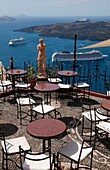 Looking down at romantic restaurant and the sea with statue in Santorini Greece in Greek Islands
