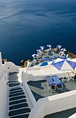 Looking down mountain stairs onto balcony with umbrella in Fira in Santorini Greece in Greek Islands