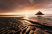 Impressive sunset above the famous monastery Mont-Saint Michel, built in the 10th century, Mont-Saint Michel with tide flat in the foreground, Normandy, France