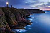 Cap Frehel lighthouse at the top of the 70-meter high cliffs in north-west France in blue light at dusk, Brittany, France