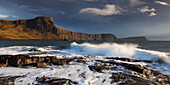 Incoming surf with view to the impressive cliffs of Waterstein head at the western end of the Isle of Skye, Scotland, United Kingdom
