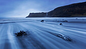 Long exposure on Talisker beach in the blue twilight with view towards the impressive cliffs on the Isle of Skye, Scotland, United Kingdom