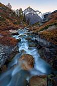 First daylight above the Taeschalp with mountain stream and alpenglow on the summit of the Weisshorn, Valais, Switzerland