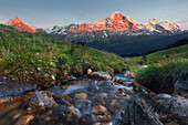 Last daylight above a mountain pasture with a stream, alpenglow on the mountain peaks of Schreckhorn, Finsteraarhorn, Eiger, Mönch and Jungfrau in the background, Bernese Oberland, Switzerland