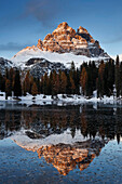 View from the south-west to the impressively illuminated Tre Cime di Lavaredo with their reflection in Lago de Antorno, South Tyrol, Italy