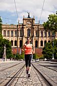 Young woman jogging over Maximilian bridge, Maximilianeum in background, Munich, Bavaria, Germany