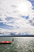 Young woman jumping from a floatable platform into Lake Starnberg, Bavaria, Germany