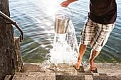 Man scooping water from Lake Starnberg, Bavaria, Germany