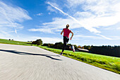 Woman jogging along a road, Munsing, Bavaria, Germany