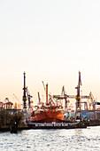 Blohm unf Voss Werft dockyard, sunset over the habour of Hamburg at the Landungsbruecken, Hamburg, Germany