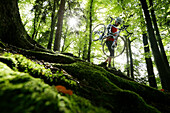 Man cyclocross touring in autumn, carrying bicycle on shoulder, Oberambach, Munsing, Bavaria, Germany