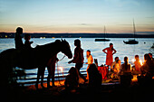 Adults and children with torches at lakeshore, lake Starnberg, Bavaria, Germany