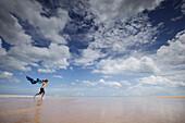 Boy holding a scarf over head running along beach, Tangalle, Hambantota District, Southern Province, Sri Lanka