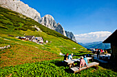 Hikers resting at an alpine lodge, Foelzalm, Styria, Austria