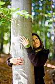 Young woman embracing a tree, Styria, Austria