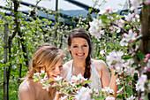 Two young women between flowering apple trees, Riegersburg, Styria, Austria