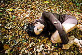 Young woman lying on autumn leaves, Styria, Austria