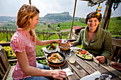 Two young women having lunch, Riegersburg castle in background, Riegersburg, Styria, Austria