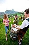 Two young women enjoying local specialties in a vineyard, Riegersburg, Styria, Austria