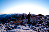 Two hikers at summit of Hochschwab mountain at sunrise, Hochschwab, Styria, Austria