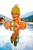 Young woman wearing a wolly hat holding a cup while bathing in a pool, Fladnitz an der Teichalm, Styria, Austria