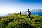 Hikers arriving summit cross of Gasselhoehe, Schladminger Tauern, Styria, Austria