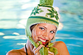 Young woman wearing a wolly hat in a swimming pool, Styria, Austria