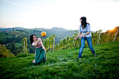 Young women throwing a pumpkin, Styria, Austria