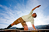 Young man doing yoga wearing traditional Austrian outfit, Styria, Austria